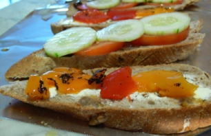 Sliced Walnut Bread with Pickle Cream Cheese Tomato Cucumber and Bell Peppers