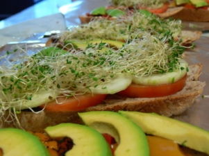 Sliced Walnut Bread with Pickle Cream Cheese Tomato Cucumber Bell Peppers Avocado and Alfalfa