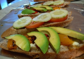Sliced Walnut Bread with Pickle Cream Cheese Tomato Cucumber Bell Peppers and Avocado